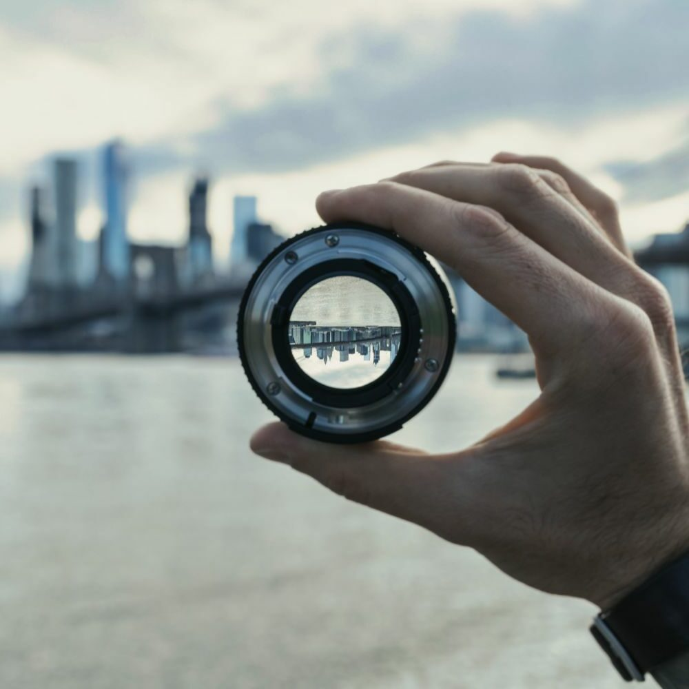 a hand holding a camera lens where you can see an upsidedown city